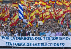 People hold Spanish flags as they protest during a march in Madrid